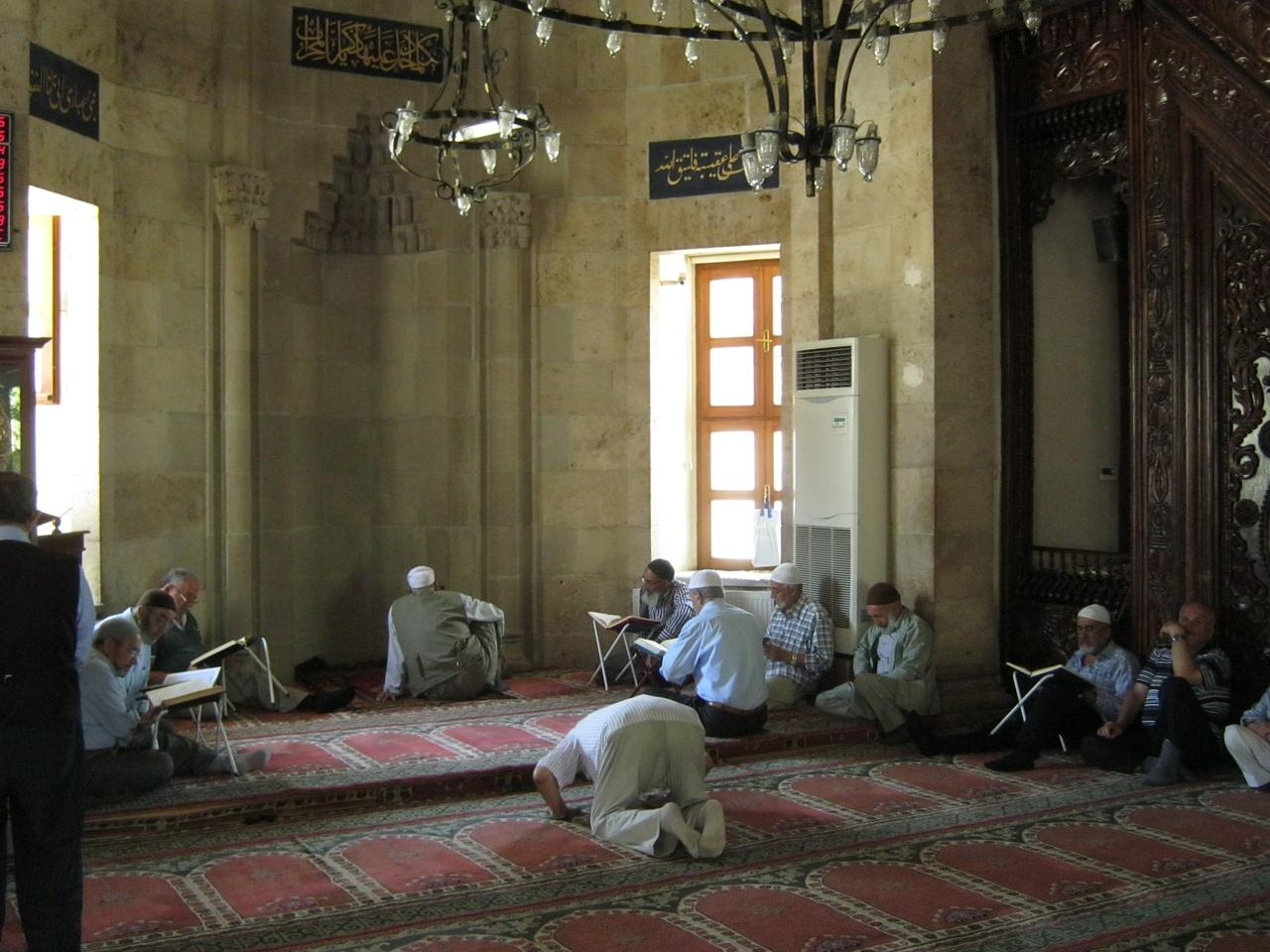 Дюжина мужиков сидят и читают Корант, а один за всех молится.